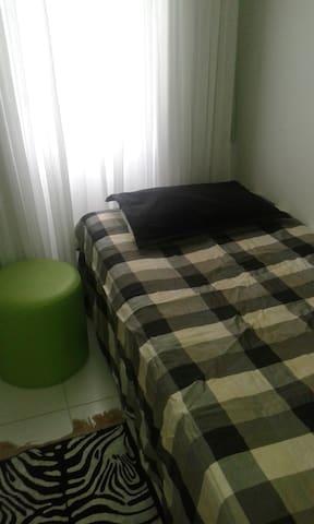 quarto de solteiro com colchão extra e ventilador