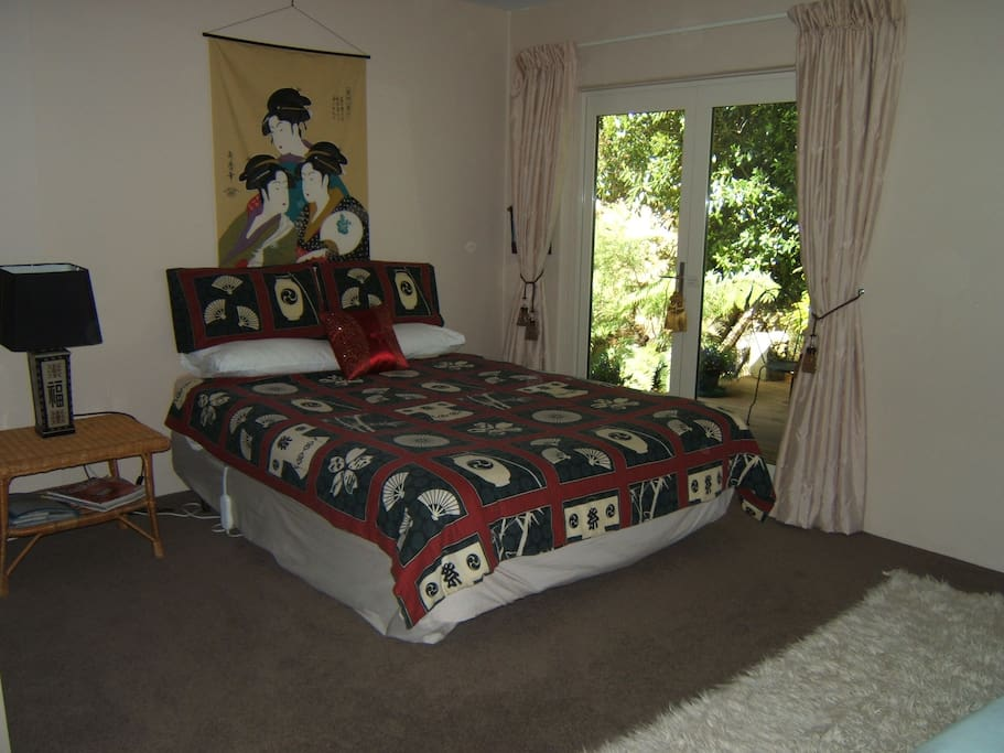 Comfortable large queen bedroom with sunny private deck
