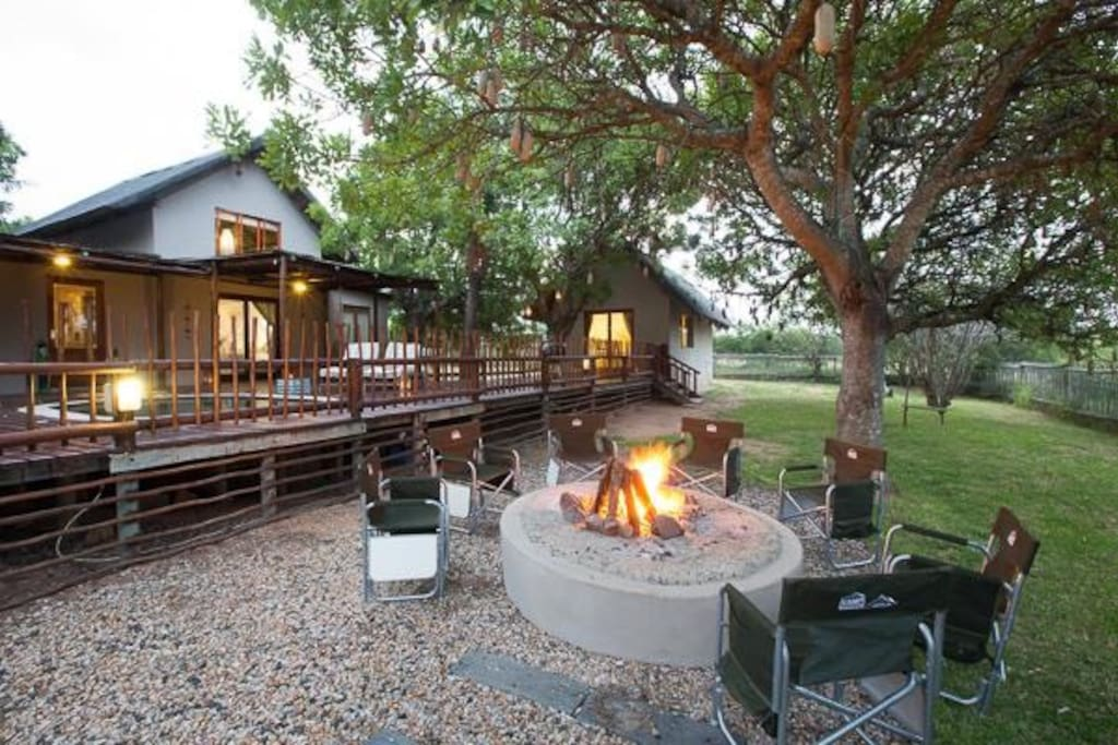The thatched house is surrounded by large Marula and Sausage trees and is set around a raised deck.