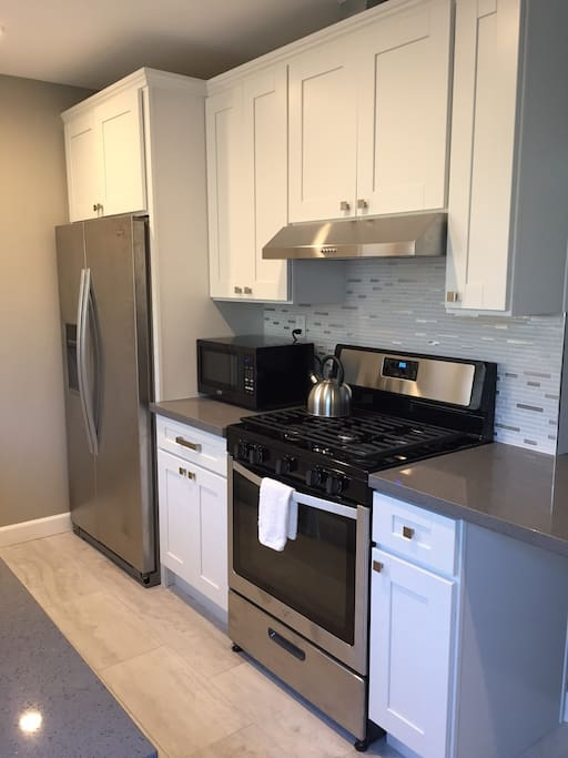 Stainless steel appliances, full size refrigerator, gas stove, microwave and kitchenware