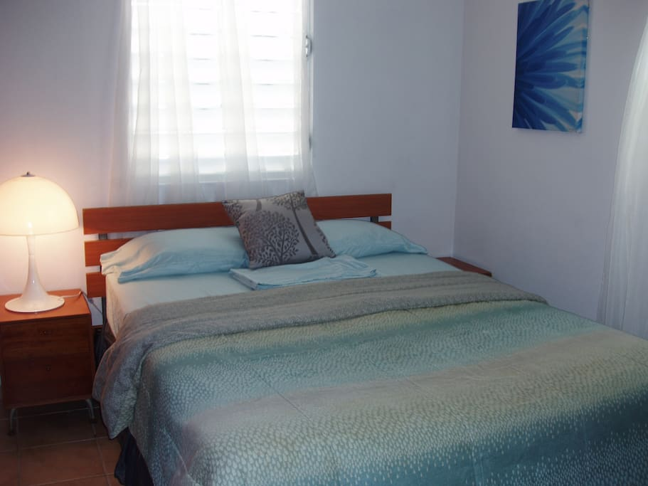 Separate bedroom with queen size bed, air conditioner, sheets and pillows.