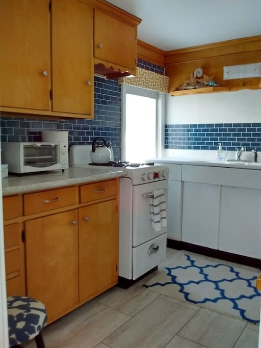 Kitchen has fridge, microwave, toaster oven and breakfast nook.
