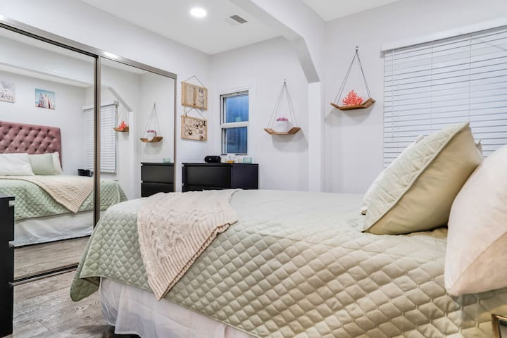Bedroom with a queen bed, two dressers, and a full size walk in closet
