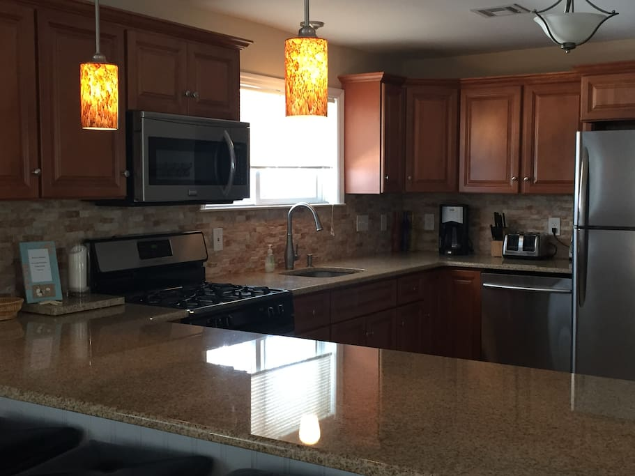 Open concept kitchen and family room with granite countertops and stainless steel appliances.