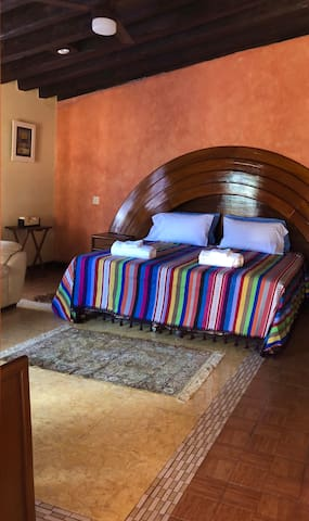 Upper Bedroom with wooden headboard rainbow shape. Direct access to the terrace on the second level.