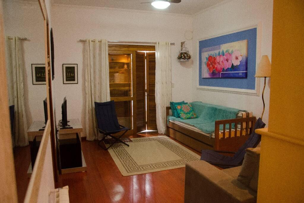 Living com sofa e cama auxiliar com porta que dá para a varanda e churrasqueira privadas.