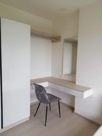 ภายในห้องนอน มีตู้เสื้อผ้า โต๊ะเครื่องแป้ง และเตียงนอน พร้อมทีวี