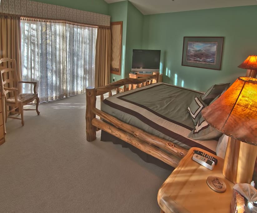 Master bedroom with view of river. Hear the sounds of the river from bed.