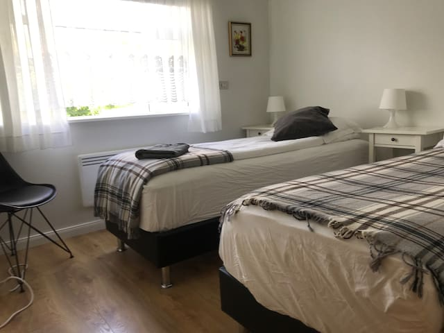 Bedroom 3 has two single beds, chair,  mirror and hangers