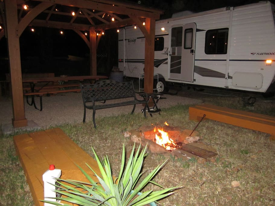 Fire pit with benches next to lights on Gazebo