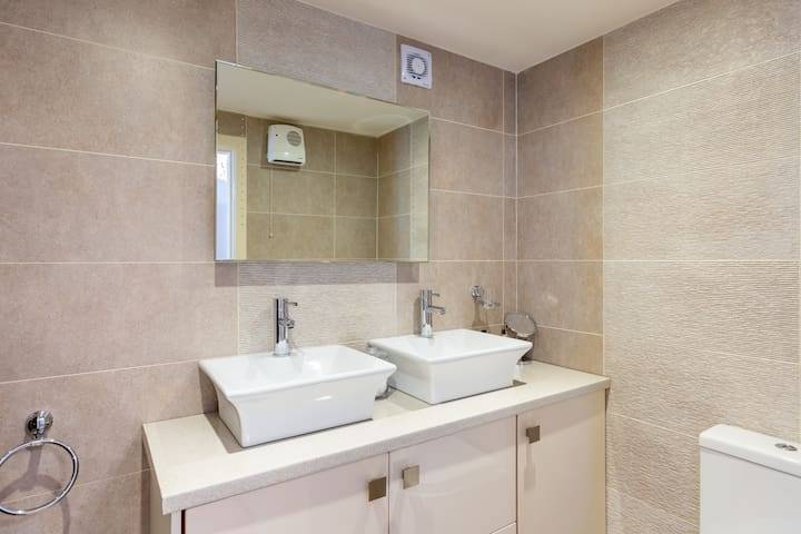 """Luxurious Ensuite. Decorated in a soothing palette of tranquil tones and richly textured porcelain tiles. Contemporary style. """"beautiful bathroom with big powerful shower!"""" Twin sinks, 100% cotton towels."""