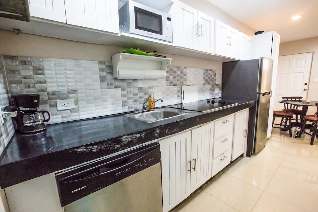 Chefs kitchen, with brand new appliances - microwave, toaster oven, coffee maker, frenchpress, nice utensils and cutlery and polished concrete counters - cook a gourmet meal in your condo with a 4-burner stovetop and a well-stocked kitchen.