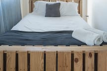 Queen Bed in Upper Level. Also made from pallets