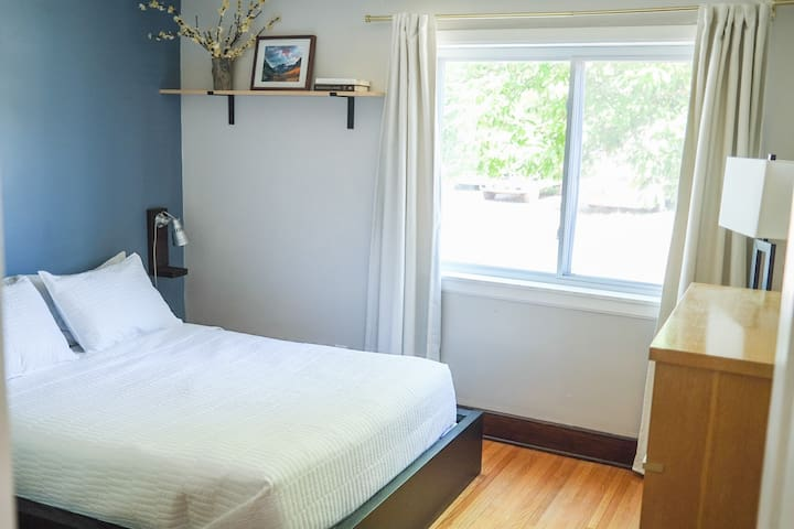 The main bedroom has a queen bed, blackout curtains, a dresser and a closet.