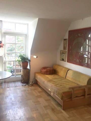 Stue med gæsteseng og udgang til balkon