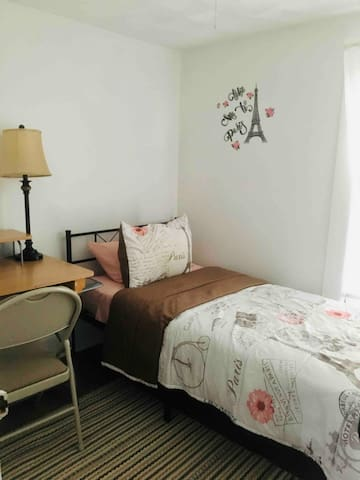 Small bedroom with twin size bed and desk for work space.