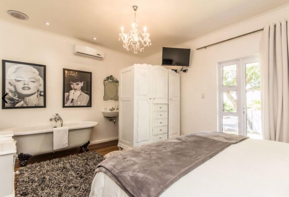 Bedroom 2 has 2single beds or can be a kingsize a bed, aircondioning, TV with all DSTV channels , and en-suite/ open plan bathroom with basin, toilet and Victorian style bath. The bedroom also has its own patio looking out onto the front garden.