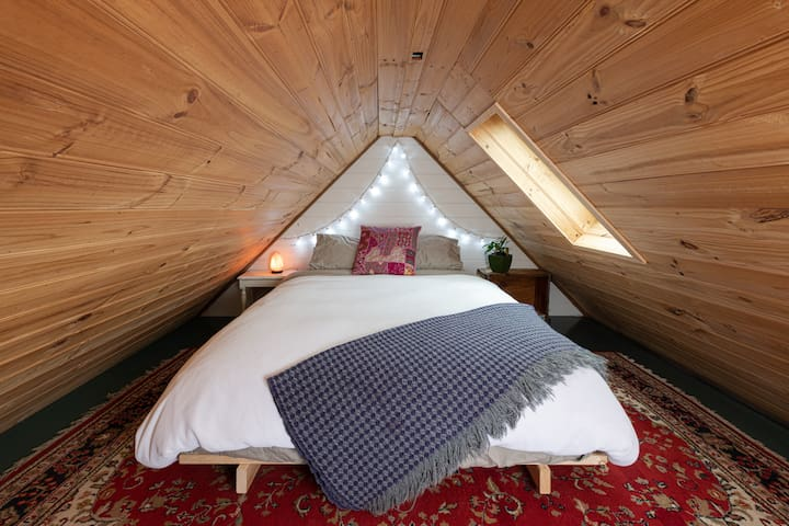 The cozy mezzanine bedroom with queen size bed.  The roof height at it's peak is 170cm, make sure to duck if you're tall!  Window opens to catch the breeze or to watch the stars at night.