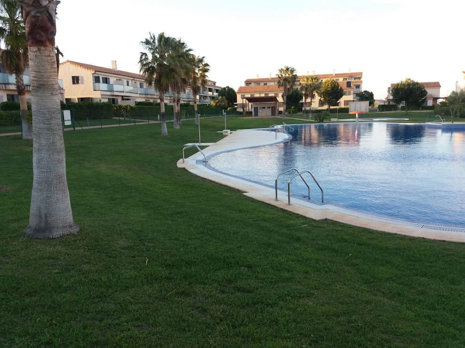 Solarium piscina con césped natural