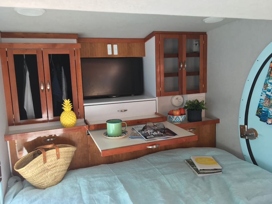 TV which rotates to also appears through the kitchen! Slide out table. Hanging space and drawers/shelves