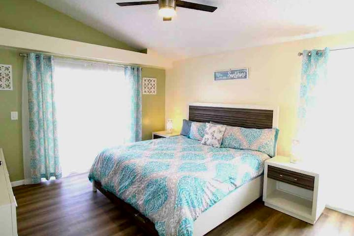 Master Bedroom located on first level featuring a KING bed laying out on premium vinyl laminate floor, with a 42in wall mounted flat screen smart TV, ceiling light/fan, with private access to Pool deck