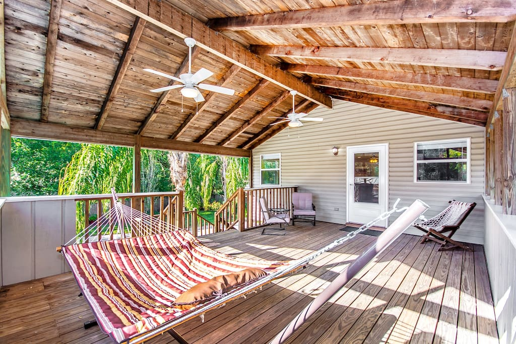 Spacious deck has ceiling fans, plenty of light, a sitting area, and a hammock perfect for relaxing.