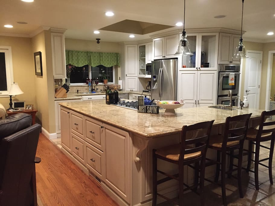 New kitchen with double ovens, granite countertops and stainless steel appliances.