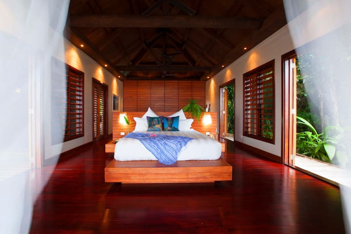 Master bedroom opens to private jungle garden and ocean view deck.