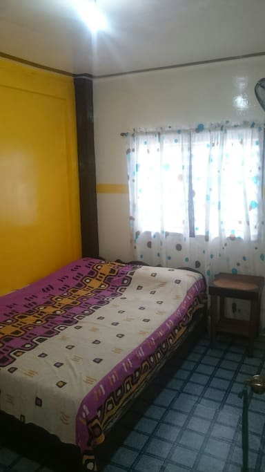 Room with queen size bed. Electric fan in the room.