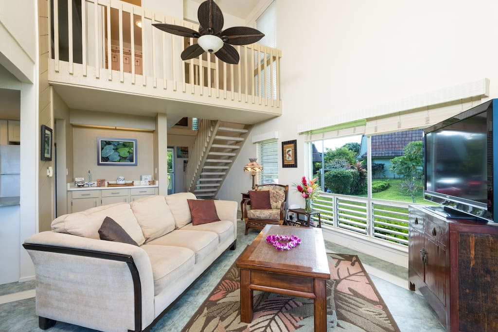 Your comfortable living room with a view of the Hanalei Mountains off beyond the landscaped green.