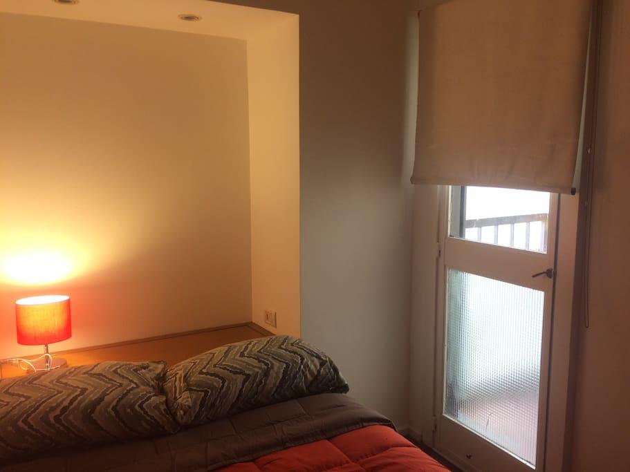 Dormitorio con cama de dos plazas, luz y pequeño balcón.  Aire acondicionado.