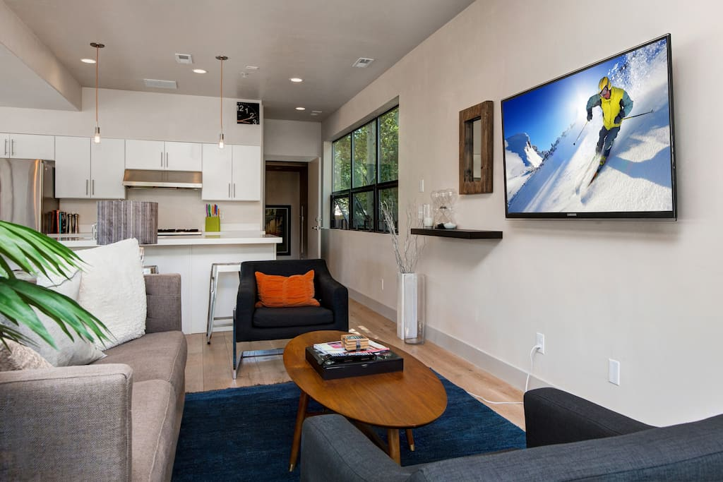 "The bright living room features plenty of seating, including a sleeper sofa, and a 55"" flat-screen TV."