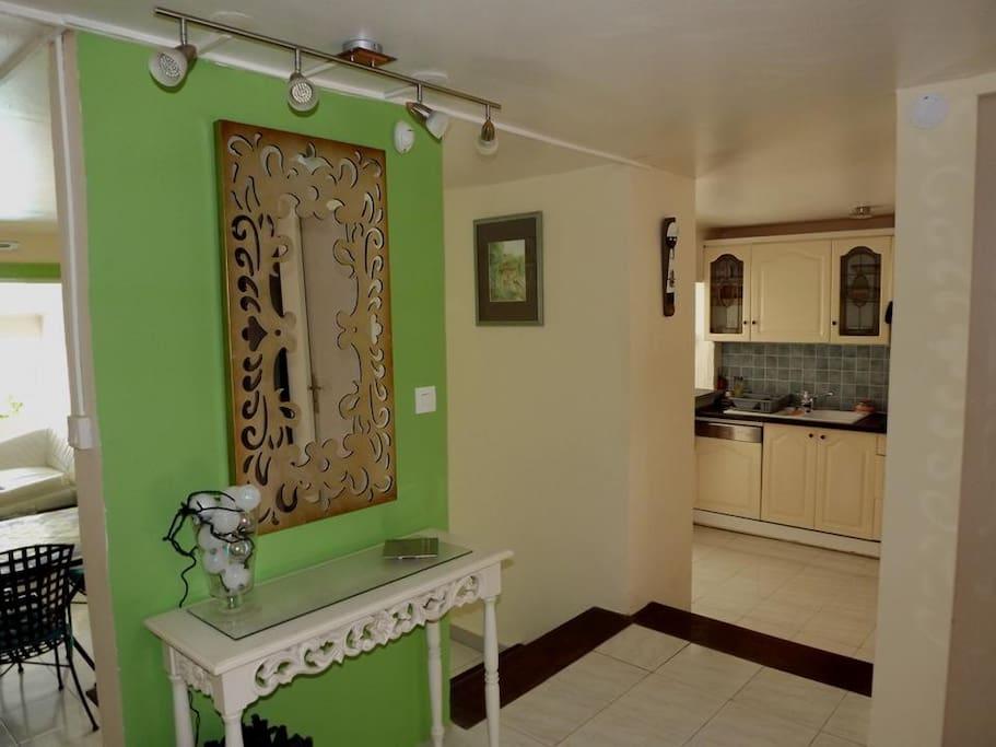 Entrée principale distribuant à des niveaux différents sur la cuisine bien équipée, le vaste séjour et l'escalier d'accès à l'étage (coin nuit/salle d'eau et terrasses supérieures)