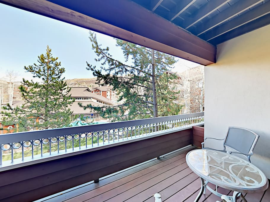 Private balcony overlooking the pool and clubhouse, with mountains beyond. Condo professionally managed and maintained by TurnKey Vacation Rentals.