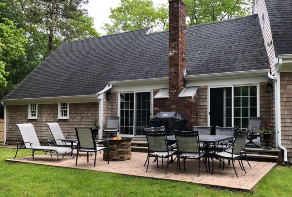 Fenced off backyard with patio, grill, table, chairs and fire pit