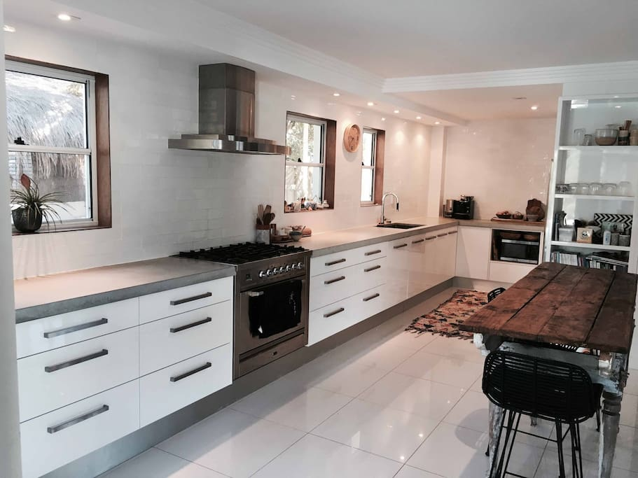Galley style chefs kitchen with concrete benchtop, gas stove and double fridge