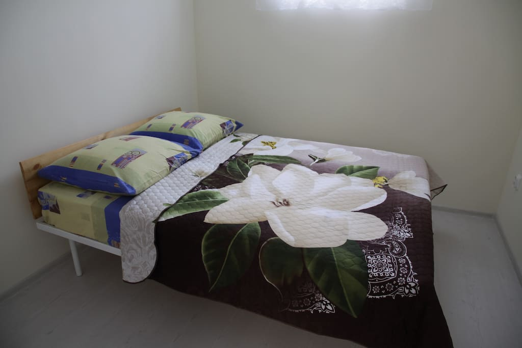 В маленькой комнате двухспальная кровать с ортопедическим матрацем