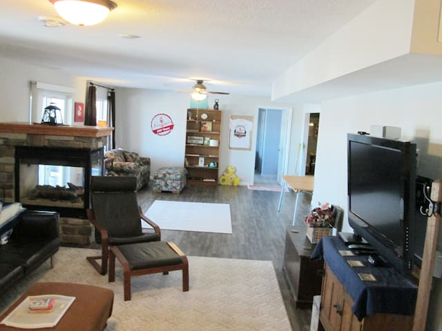 """Livingroom with 42"""" Roku/Netflicks/Sling cable/dvd player, 2 leather couches, fireplace, leather chair, footstools, two large windows and sliding glass door to large patio with small grill, fire pit and seating, seasonal hammocks and table/4 chairs."""