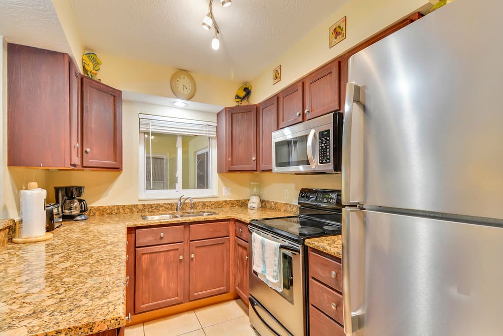 Granite countertops and stainless steel appliances shine in the well-equipped kitchen.