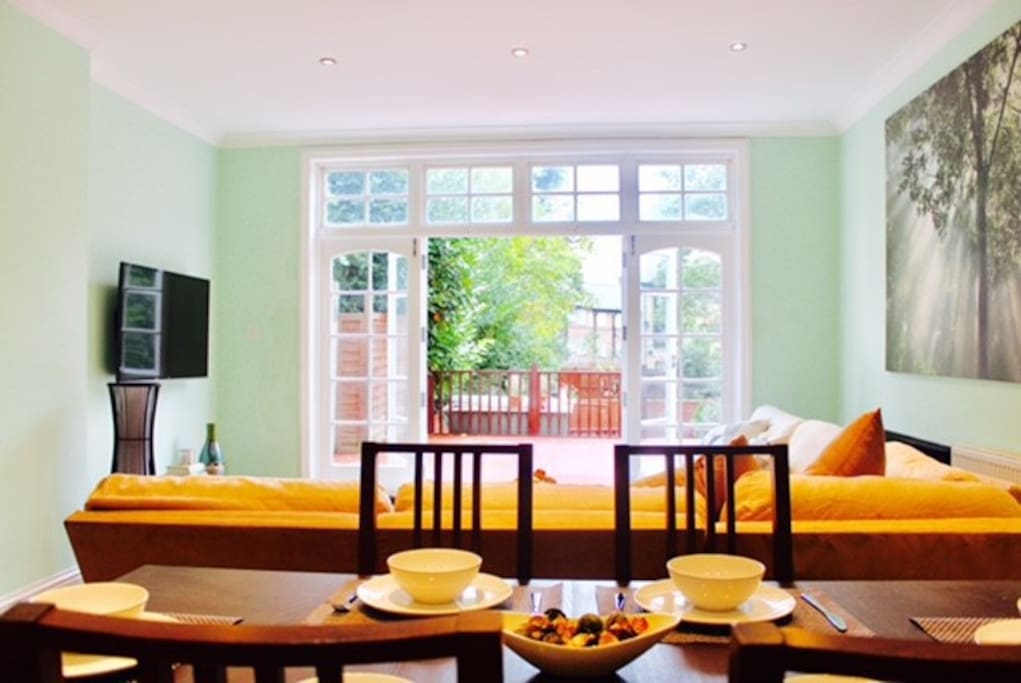 Beautiful light airy open plan living room with high aspect ceilings and French Doors leading onto Decking area.