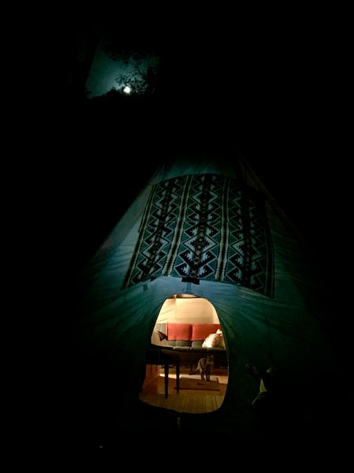 Tepee under a full moon through the oak trees