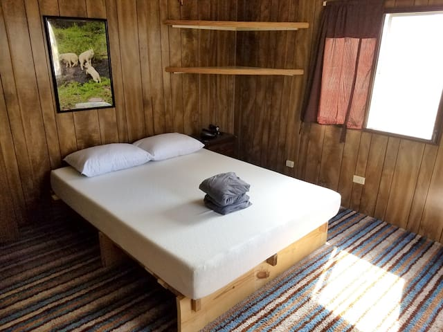 Room with a view of mountains and lake. Handmade bed frame built from reclaimed wood.