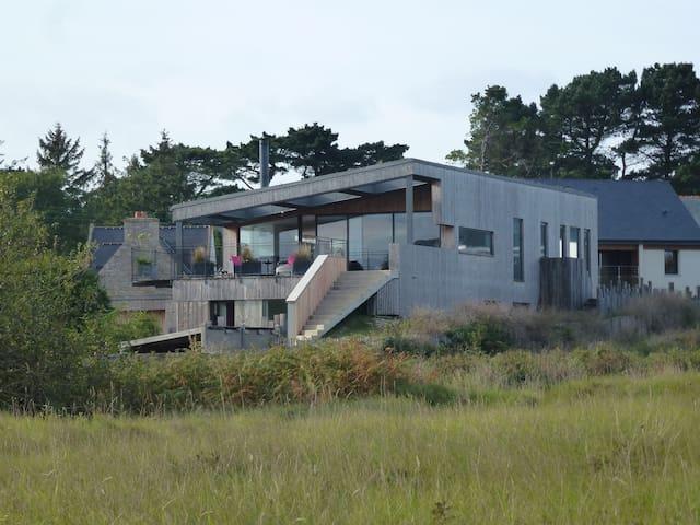 Une grande maison en bois au bord de l'eau ...