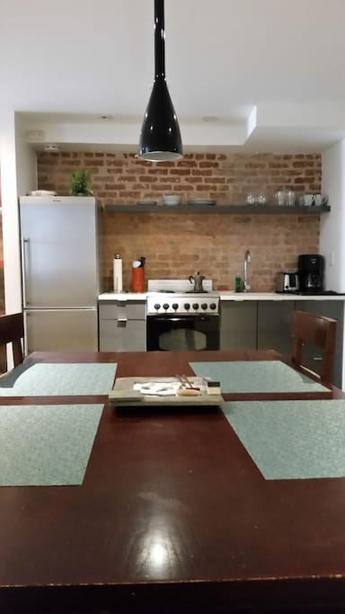 Kitchen includes refrigerator, oven, stove, toaster, coffee maker, and essential pots, utensils and dishes.