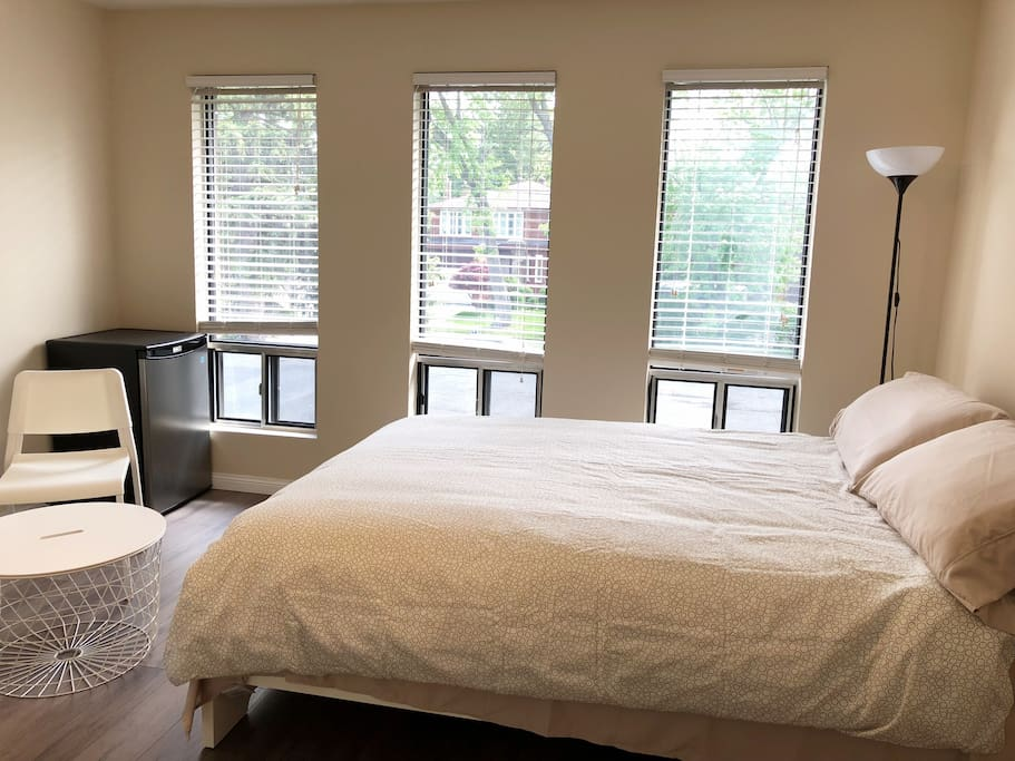 Furnished room with fresh linens, mini refrigerator, tea table, built-in closet, and night stand