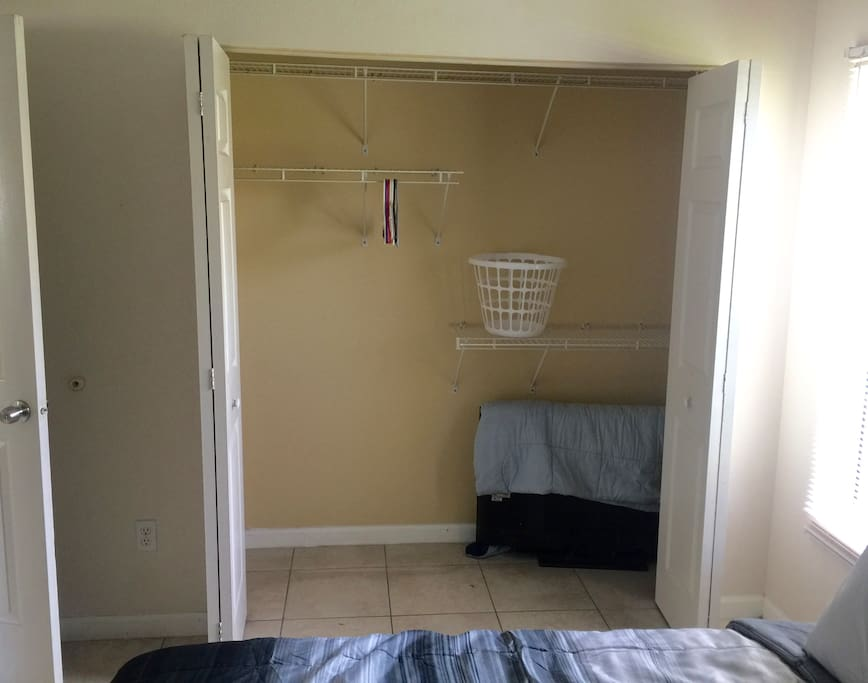 Large closet with hangers and laundry basket.