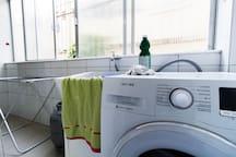 Área de serviço com máquina de lavar e secar pronta para seu conforto