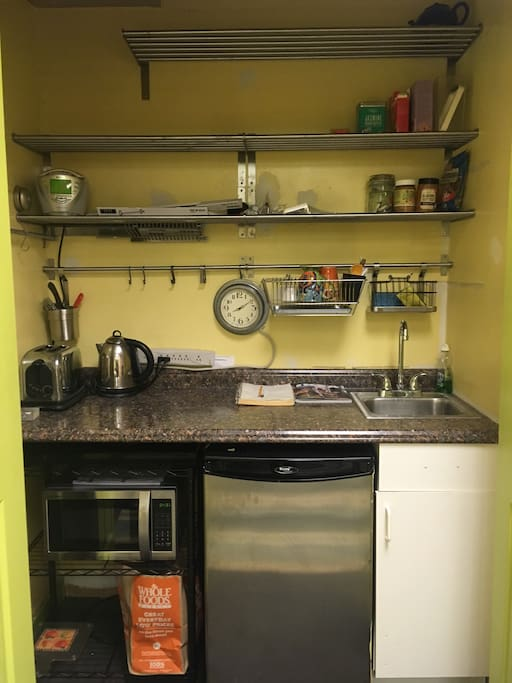 Simple kitchen with a coffee maker, microwave oven, small fridge, sink