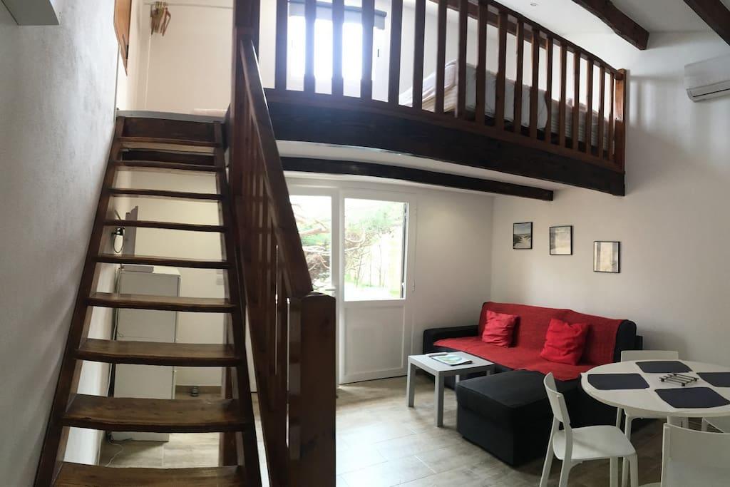le salon avec le canapé lit et la mezzanine (et son lit) avec vue mer