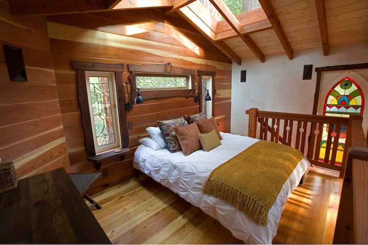 Loft bedroom with queen bed. Skylights above bed looking up to the trees